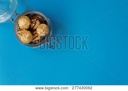 Sweets In Golden Foil And Cookies With Chocolate In A Glass Jar On Blue Background, Copy Space, Top