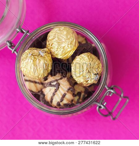Square Photo Of Jar With Sweets And Cookies On Bright Pink Background, Top View