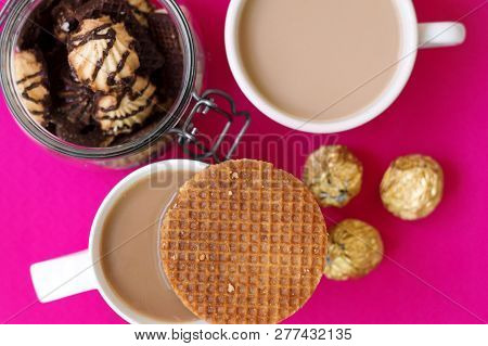 Two Cups With Coffee, Caramel Waffles, Jar With Cookies And Sweets Wrapped In Golden Foil, Top View,