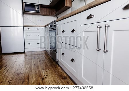 poster of Stylish kitchen interior design. Luxury modern kitchen furniture in grey color and steel oven,fridge, sink, wooden tabletop. Gray cabinets in scandinavian style. Home renovation