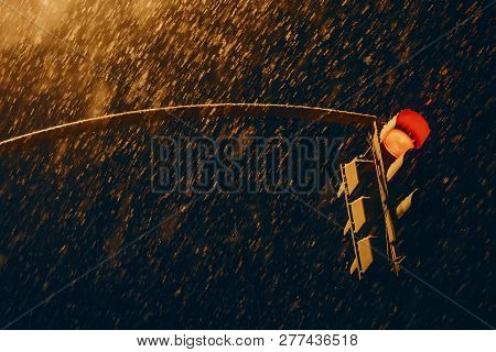 Red Traffic Signal In Dark Time Close Up. Traffic Light At Strong Snowfall. Huge Snowflakes Above Ro