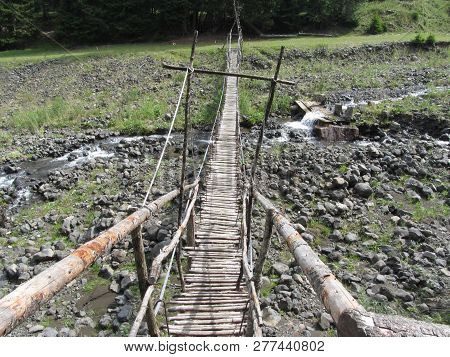 Wooden Pedestrian Suspension Bridge Over The Torrent . South Tyrol, Italy