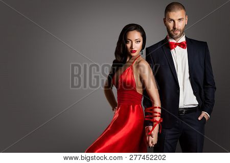 Fashion Couple, Woman And Man Arms Bounded By Ribbon, Models Studio Portrait In Red Dress And Black