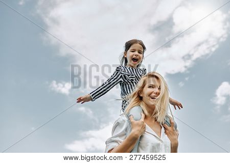 Happy Little Funny Daughter On A Piggy Back Ride With Her Happy Mother On The Sky Background. Loving