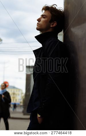 Portrait Of A Handsome, Attractive, Young Man In A Blue Suit, Coat, In The City. Pensive And Sad, Wa