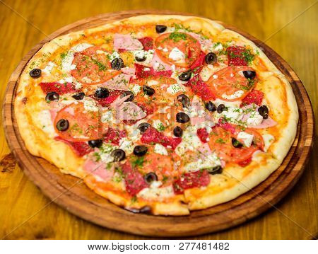 Delicious Hot Pizza On Wooden Board Plate. Food Delivery Service. Pizza With Pepperoni, Tomatoes And
