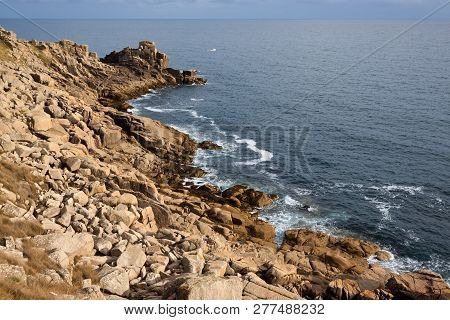 Rocky Coastline Blue Sea And Sky With Small Boat In The Distance. Space For Copy