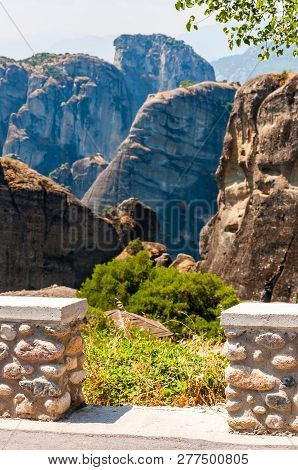 Stone Masonry Fence On The Cliff With Scenic Landscape View On Meteora Rock Formations Cliffs And Pe
