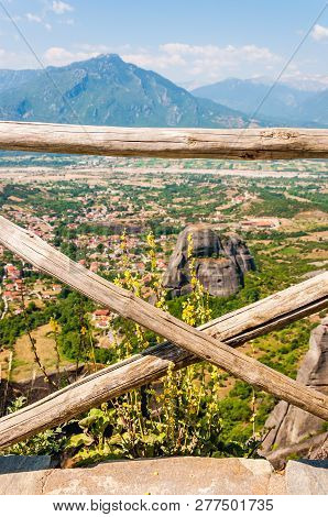 Panoramic View Through The Wooden Logs Fence On Scenic Meteora Rock Formations Landscape And Valley