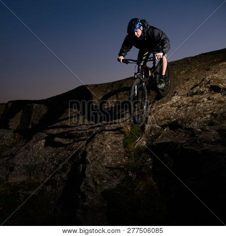 Cyclist Riding the Bike on the Rocky Trail at Night. Extreme Sport and Enduro Biking Concept.