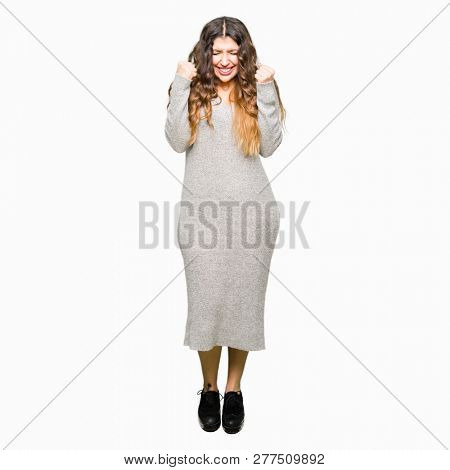 Young beautiful woman wearing winter dress excited for success with arms raised celebrating victory smiling. Winner concept.