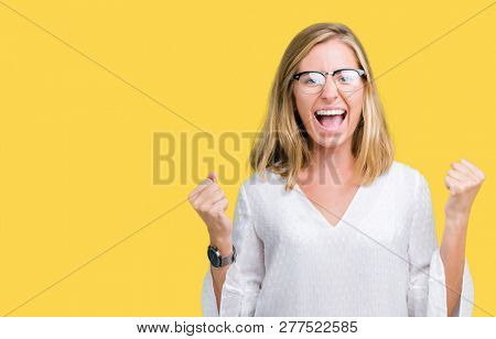 Beautiful young woman wearing glasses over isolated background very happy and excited doing winner gesture with arms raised, smiling and screaming for success. Celebration concept.