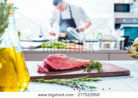 Chef In Restaurant Kitchen Cooking,he Is Cutting Meat Or Steak