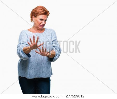 Atrractive senior caucasian redhead woman wearing winter sweater over isolated background disgusted expression, displeased and fearful doing disgust face because aversion reaction. With hands raised