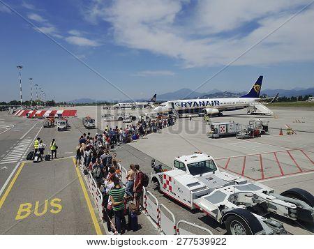 Bergamo, Italy - July 17 2018: Milan Bergamo Airport Tarmac Passengers. Travelers With Luggage At Ap