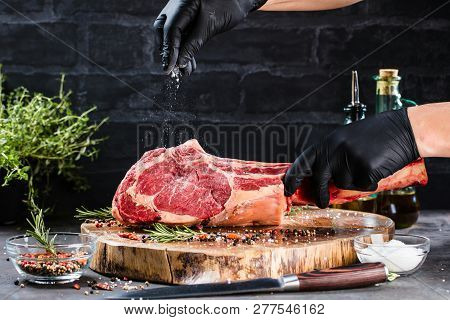 Male Hands Of Butcher Or Cook Holding Tomahawk Beef Steak On Dark Rustic Kitchen Table Background.