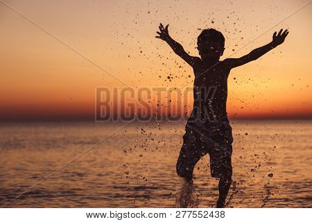 One Happy Little Boy Playing On The Beach At The Sunset Time.