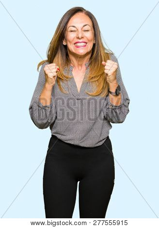 Beautiful middle age business woman excited for success with arms raised celebrating victory smiling. Winner concept.