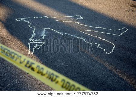 Crime Scene. Chalk Outline. KILLER CLOWN Chalk Outline in the street.  Clown with hand gun chalk outline. Yellow Sheriff Do Not Cross Tape.