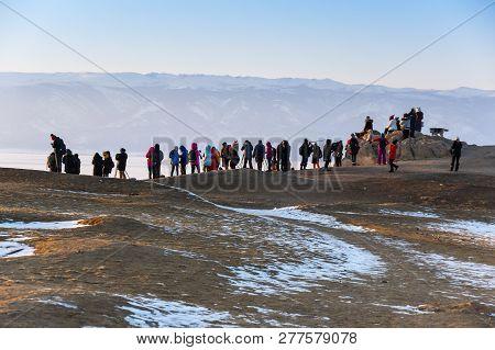 Tourists Watching The Sunset On The Coast Of Baikal Lake, Siberia, Russia