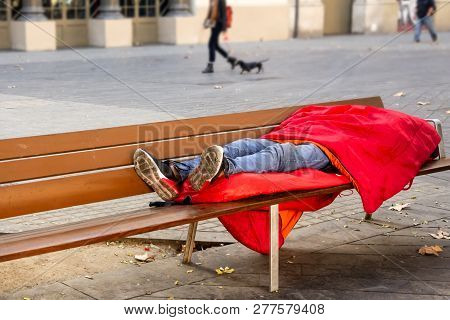 A Homeless Man Sleeping On A Bench In A Red Sleeping Bag On The Street. Cheap Budget Traveling