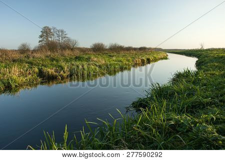 Green Grassy Shore And A Calm Clean River. Poland, The Uherka River