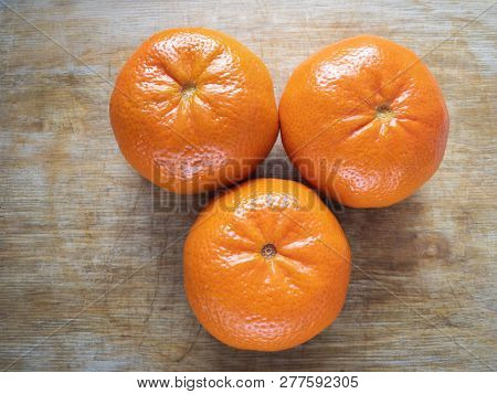 Top View On Three Tangerine On Wooden Cut Board