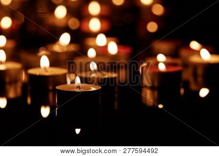 Abstract background from burning candles with reflections on a black background with copy space.