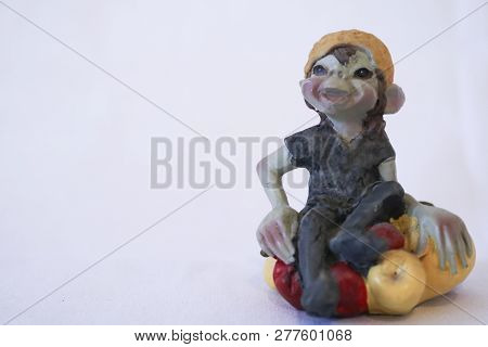 Goblin statue with fruits, white background, collectors items poster