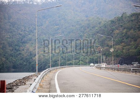 Driving On Concrete Road Along The Water Reservoir Dam In The Area Of Rich Natural Forest Tree Mount