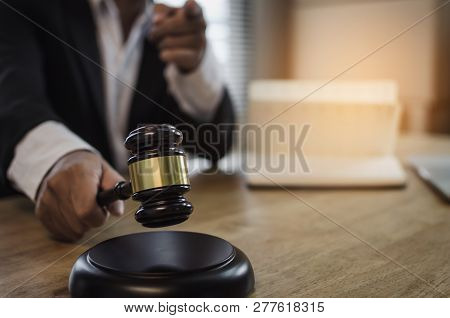 Justice Lawyer In Black Suit Pointing Finger And Knocking Wooden Judge Gavel With Documents On Workp