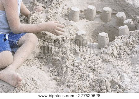 A Little Boy Build Sand Castle On Beach