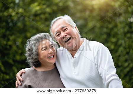 Portrait Of Asian Senior Couple Laughing At The Park. Happy Elderly With Positive Feeling At Outdoor