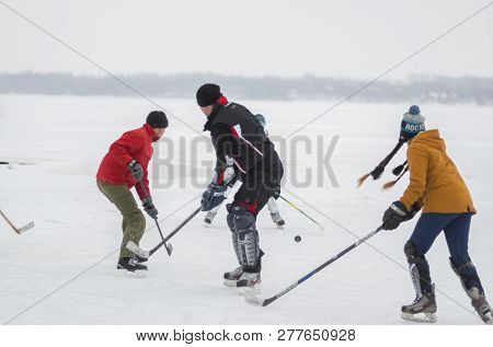 Dnipro, Ukraine - January 28, 2018: Group Of Active People Including Girl Playing Hokey On A Frozen
