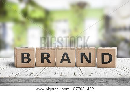 Brand Sign Spelled With Wooden Cubes On A Table In A Bright Green Room