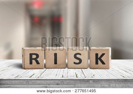 Risk Sign On A Wooden Desk With Red Lights On In A Hallway