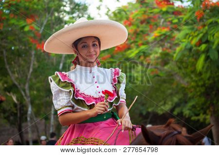 Xcaret, Mexico - July 19, 2011: Woman at traditional Mexican Fiesta Charra Show in Xcaret Park with charros display their acrobatic skills on horseback.