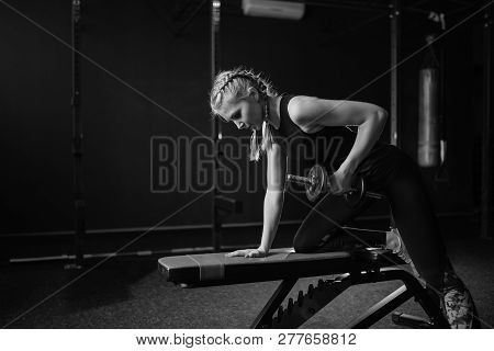 Sporty Fit Woman Bodybuilder In Gym Lifting Dumbbells On Bench. Black And White. Copy Space.