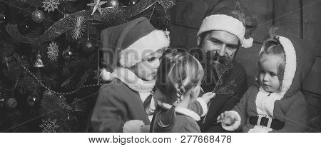 Santa claus kid and bearded man at Christmas tree. Christmas happy children and father. New year small girl and man, fairytale. Xmas party celebration, fathers day. Winter holiday and vacation. poster