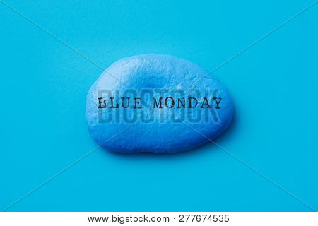 closeup of a stone painted blue with the text blue monday written in it, on a blue background