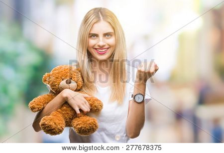 Young beautiful blonde woman holding teddy bear over isolated background screaming proud and celebrating victory and success very excited, cheering emotion