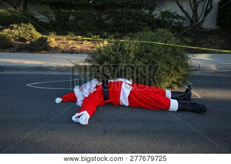 Los Angeles Crime Scene.  Santa Claus lays dead on the ground with a Police Chalk Line and Sheriff Do Not Cross Yellow Crime Scene Tape. Christmas Crime Scene. Dead X-Mas Tree on top of Santa's body.