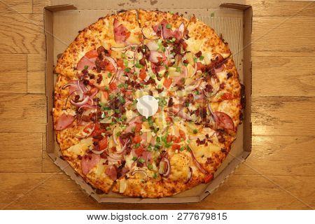 Pizza. Hawaiian Pizza in cardboard delivery box. Pineapple Pizza. Pizza with pineapple, ham, onions, cheese, tomatoes, bacon, and sauce.  Wooden Table background. Room for text overlay.