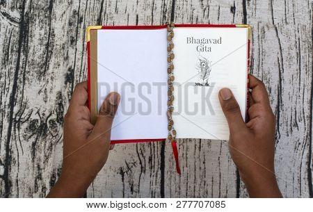 Maski,karnataka,india - December 29,2018 : Reading Bhagavad Gita With Hands On Textured Background