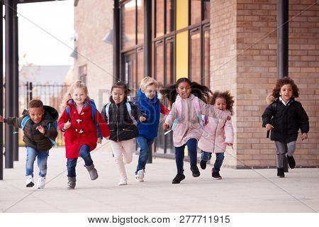 A happy multi-ethnic group of young school kids wearing coats and carrying schoolbags running in a walkway with their classmates outside their infant school building