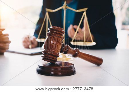 Businesswoman And Male Lawyers Having A Meeting At A Law Firm. Judge Gavel And Gold Brass Balance Sc