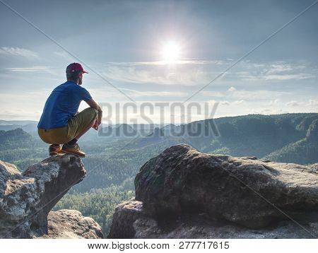 Man Risk At The Edge. Man In Training Sports Clothes  Sit On Cliff And Enjoying Far View. View Into