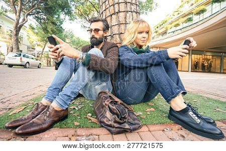 Hipster millennial couple in disinterest moment with smartphone - Apathy concept about sadness and isolation using mobile smart phone - Millenial boyfriend and girlfriend with cellphone addiction poster