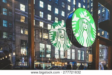 New York - March 25, 2015: Starbucks Sign At Cafe Shop By Night With Glass Reflections On Nyc Nights