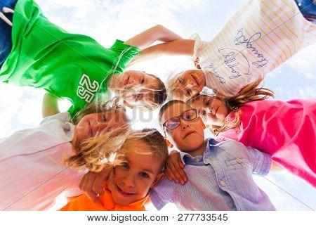 Happy Kids Hugging On Shoulders Looking Down
